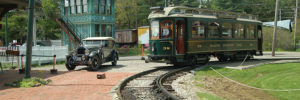 antique green trolley car and regular car